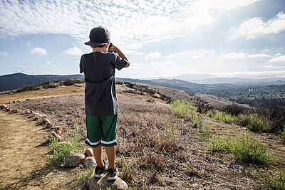 Rear view of boy looking through binoculars from footpath stone, Thousand Oaks, California USA - p429m1084590 by Ian Spanier