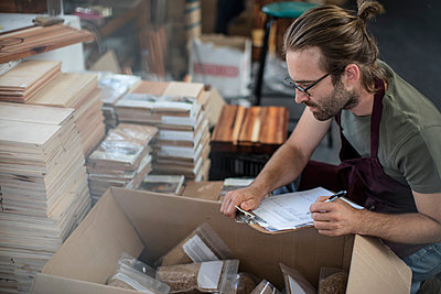 Man with clipboard checking boxed products in factory - p924m1422838 by Zero Creatives