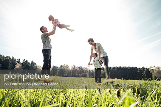 Happy family with two kids on a meadow in spring - p300m2166956 by Wilfried Feder