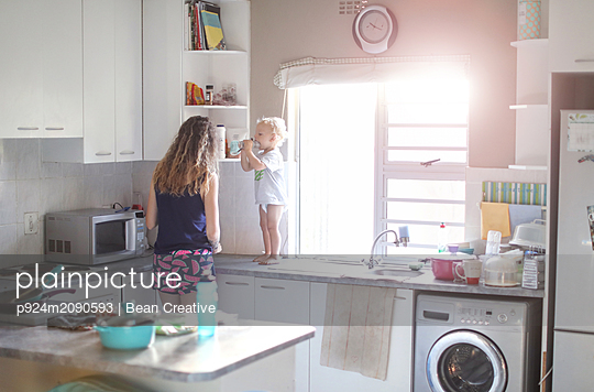 Mother and baby son preparing breakfast in kitchen - p924m2090593 by Bean Creative
