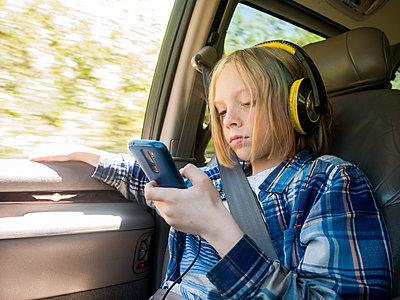 Boy using mobile phone while listening music in car - p1166m1541831 by Cavan Social