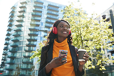 Businesswoman with disposable coffee cup day dreaming while listening music at office park - p300m2241590 by Pete Muller