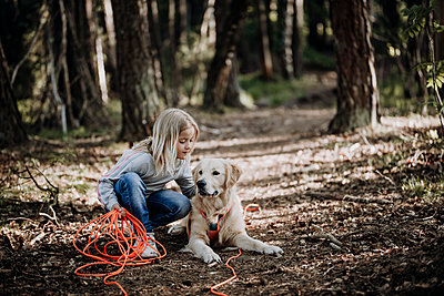 Girl with dog in forest - p312m2207705 by Anna Johnsson