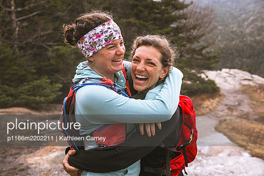 Two smiling female hikers embracing, Mt Willard, New Hampshire, USA - p1166m2202211 by Kathleen Carney