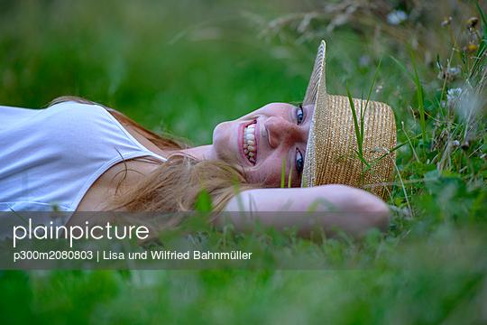 Portrait of laughing teenage girl wearing straw hat lying on a meadow in summer - p300m2080803 von Lisa und Wilfried Bahnmüller