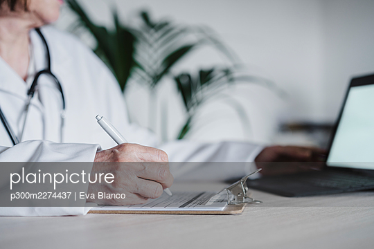 Hand of female doctor preparing report on clipboard at desk in hospital - p300m2274437 by Eva Blanco