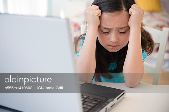 Frustrated girl using laptop - p555m1410602 by JGI/Jamie Grill