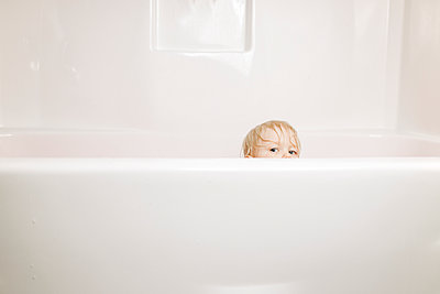 Portrait of boy peeking while sitting in bathtub - p1166m1210843 by Cavan Images