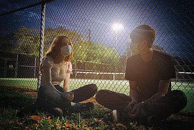 Junges Paar mit Masken an einem Sportplatz - p1694m2291714 von Oksana Wagner