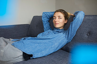 Portrait of woman wearing denim shirt relaxing on the couch - p300m1581326 von Philipp Nemenz