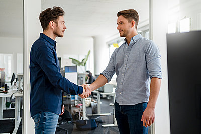 Handsome business people shaking hands in office - p300m2265222 by Daniel Ingold
