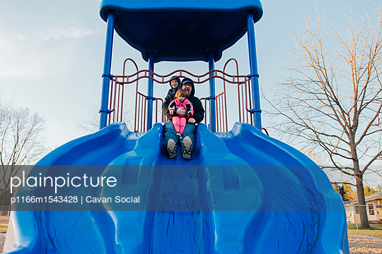 Low angle view of family playing on slide in playground - p1166m1543428 by Cavan Social