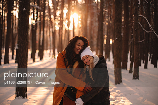 Portrait of happy lesbian couple embracing standing in park in winter - p1166m2268797 by Cavan Images