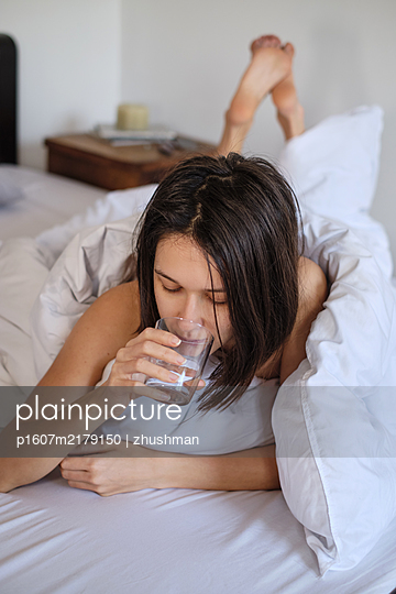 Young woman laying in her bed with a glass of water - p1607m2179150 by zhushman
