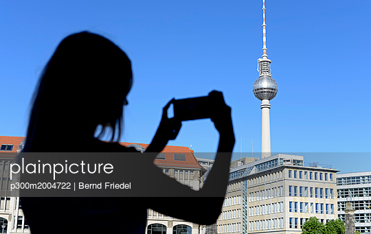 Silhouette of young woman photographing Berlin TV Tower - p300m2004722 von Bernd Friedel