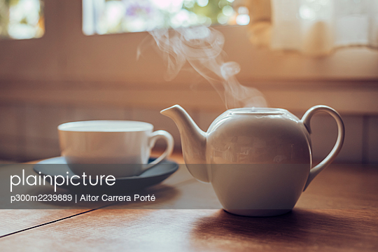 Teapot giving off smoke on top of a kitchen table - p300m2239889 von Aitor Carrera Porté