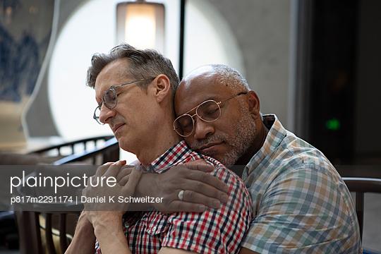 Gay couple embracing, portrait - p817m2291174 by Daniel K Schweitzer