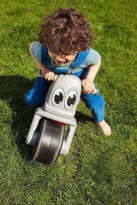 auf dem Mini-Motorrad über den Rasen - p045m1441000 von Jasmin Sander