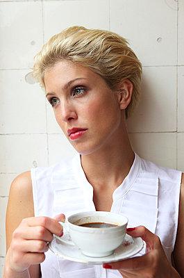 Sad young woman drinking coffee - p045m826058 by Jasmin Sander