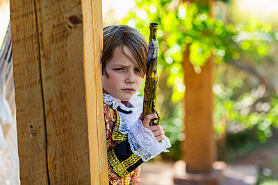 Young boy dressed as a pirate holding long pistol. - p1100m2220324 by Mint Images
