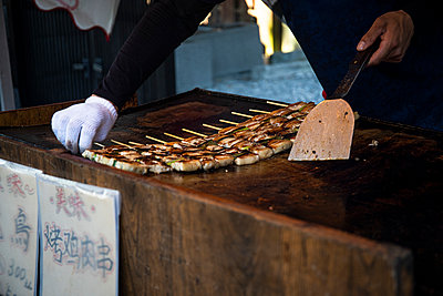 Japan, Kyoto Prefecture, Kyoto City, Hands of chef preparing yakitori at food stand - p300m2154469 by Andrés Benitez