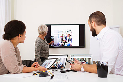 Side view of businesswoman giving presentation to colleagues in office - p426m1036610f by Maskot