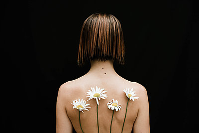 Naked woman with chamomiles on her back against black background - p1166m2111997 by Cavan Images