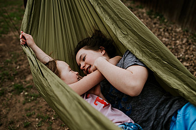 Young girls laying in hammock smiling at each other - p1166m2201352 by Cavan Images