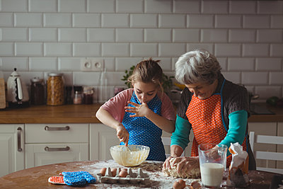 Grandmother and granddaughter preparing cookies in kitchen at home - p1315m1566658 by Wavebreak