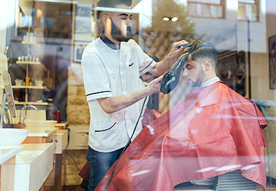 Barber blow-drying hair of a customer in a barber shop - p300m1081253f by Marco Govel