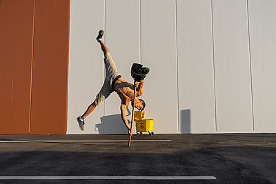 Acrobat playing with cleaning bucket and mop - p300m2012388 von VITTA GALLERY