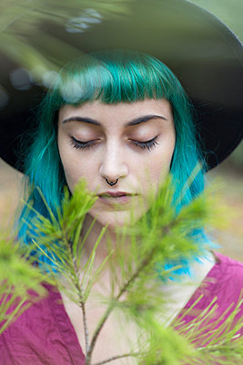 Portrait of young woman with dyed blue and green hair and nose piercing in nature - p300m2120843 by Sus Pons