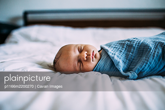 Close up of newborn sleeping on bed alone - p1166m2200270 by Cavan Images
