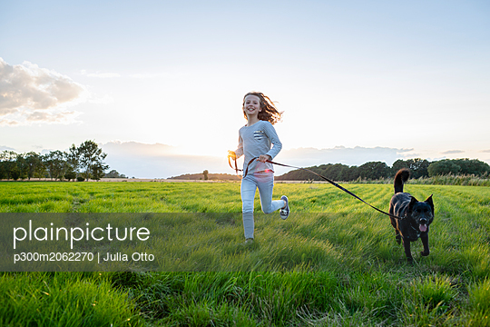 Girl with a dog running over a field at sunset - p300m2062270 by Julia Otto