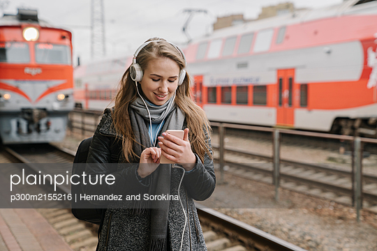 Smiling young woman standing on platform using smartphone and headphones, Vilnius, Lithuania - p300m2155216 by Hernandez and Sorokina