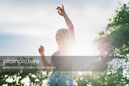 Back lit beautiful young woman dancing against sky - p300m2220551 by David Agüero Muñoz