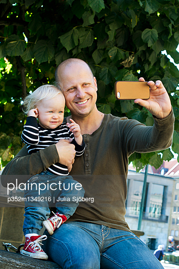 Sweden, Father and son (12-17 months) photographing self with smart phone - p352m1349216 by Julia Sjöberg