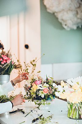 Cropped hands of florist arranging flowers at store - p1166m1474270 by Cavan Images