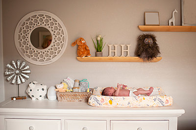 Newborn baby girl laying on changing table in diaper at home - p1166m2136703 by Cavan Images