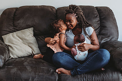 Multiracial 2 yr old kissing mom with braids holding newborn on couch - p1166m2153873 by Cavan Images