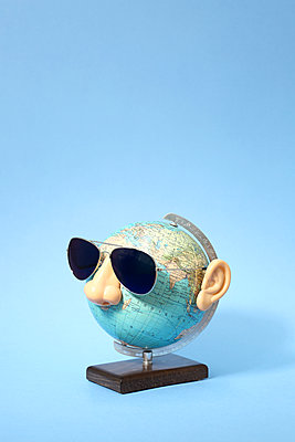 Spectacled globe against blue background - p237m1584212 by Thordis Rüggeberg