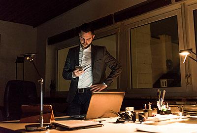 Businessman standing in office at night using smartphone - p300m1580731 von Uwe Umstätter