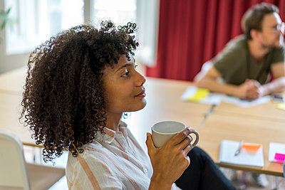 Young Afro female entrepreneur holding mug during meeting at office - p300m2264538 by VITTA GALLERY