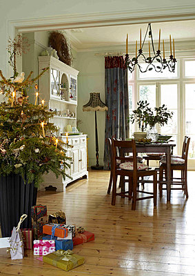 Christmas tree and presents in the open plan dining room with chandelier and table set for christmas - p349m790590 by Polly Eltes
