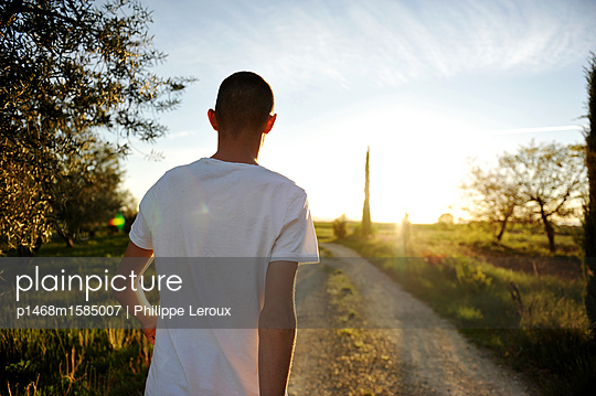 Jugendlicher mit Kurzhaarschnitt auf einem Feldweg - p1468m1585007 von Philippe Leroux