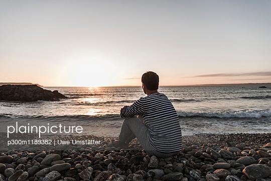France, Bretagne, Crozon peninsula, woman sitting on stony beach at sunset - p300m1189382 by Uwe Umstätter