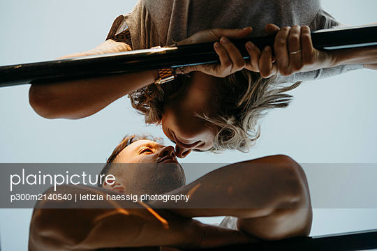 Young couple kissing each other on a climbing frame - p300m2140540 by letizia haessig photography
