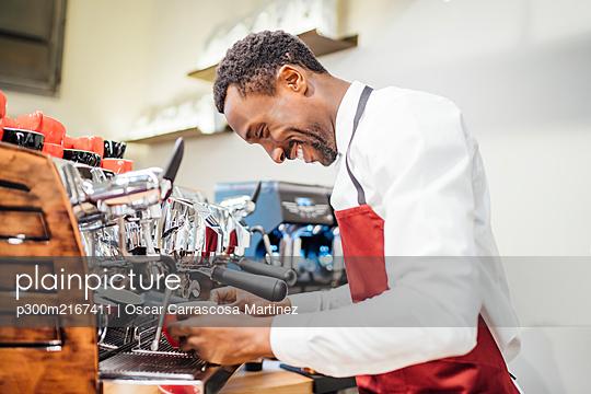 Smiling barista preparing a coffee in a coffee shop - p300m2167411 by Oscar Carrascosa Martinez