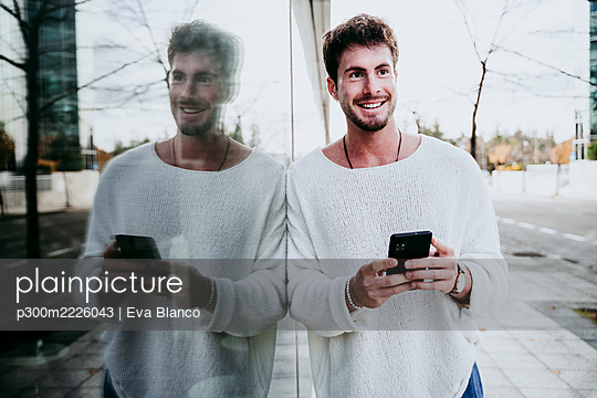 Smiling man with smart phone looking away while standing by building in city - p300m2226043 by Eva Blanco