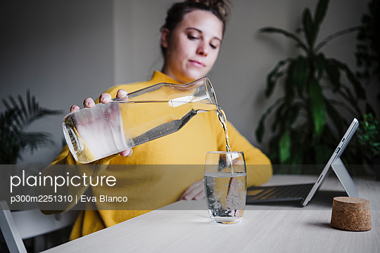 Woman pouring water in glass while sitting with digital tablet at home office - p300m2251310 by Eva Blanco
